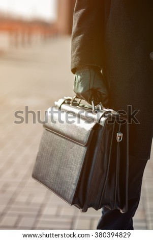 leather briefcase in his hand. young businessman walking on the street - stock photo