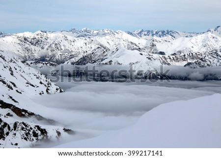 LECCO, ITALY -  a panoramic view from the top of Mount Southern Grigna:  snowy mountains and a layer of clouds. - stock photo
