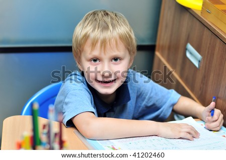 left-handed boy doing a home task in own room