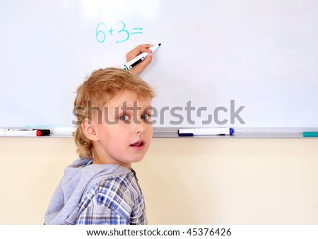left-hander little boy solving exercise on desk - stock photo