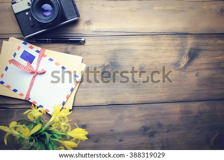 letters, camera, pen and flower on wooden table