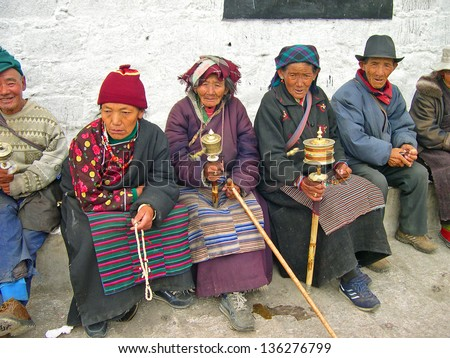 LHASA, TIBET-NOVEMBER 14: locals and pilgrims pilgrims sitting in the Jokhang temple area. This historic temple is the holiest site in Tibetan Buddhism. November 14, 2004 in Lhasa, Tibet