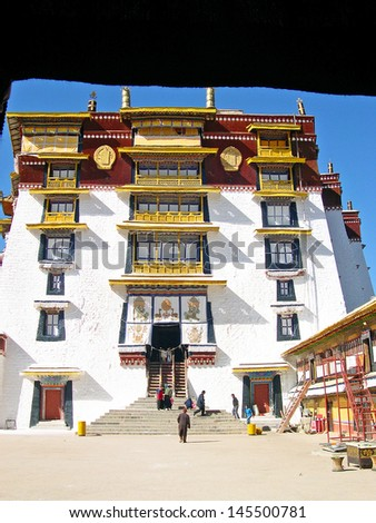 LHASA, TIBET-NOVEMBER 13:pilgrims exit the main building of the Potala palace. The Palace is the Tibet historic and political landmark. November 13, 2004 Lhasa, Tibet