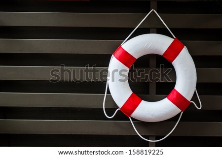 lifebuoy with rope on weathered wooden wall  - stock photo