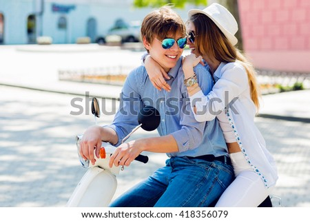 Lifestyle  portrait of young couple in love on scooter driving together. Hipster couple having fun  together  outdoor. Smiling  handsome guy and his pretty girlfriend hugging. - stock photo