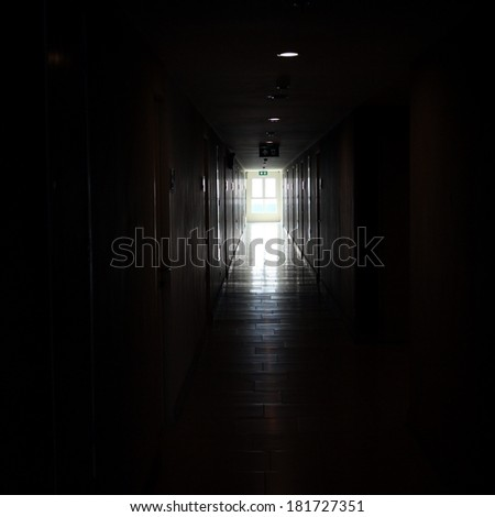 light from window in dark building walkway - stock photo