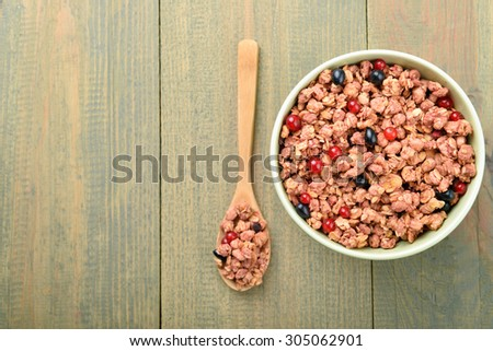 light green bowl of muesli with wooden spoon on wooden background  - stock photo