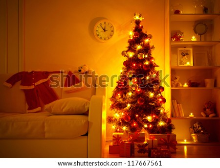 lighted Christmas tree with presents underneath in living room - stock photo