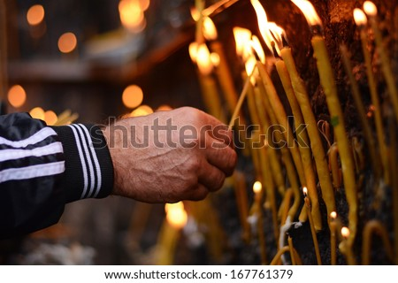 Lighting prayer candle in a church - stock photo