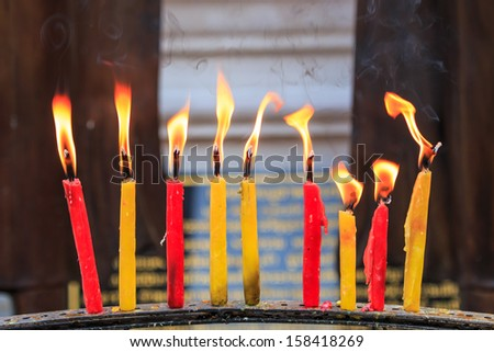 lighting prayer candle  offering, sacrificial or memorial candles lit in a church  - stock photo