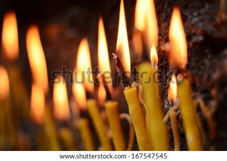 Lighting prayer candles in a church - stock photo