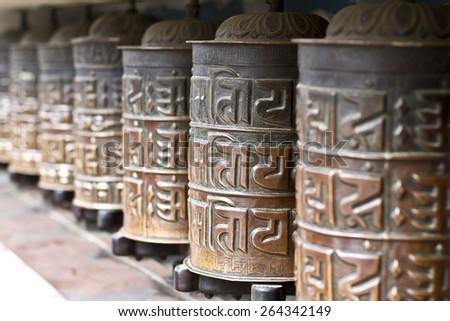 Line of Buddhist prayers wheels - stock photo