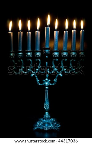 lit hanukkah menorah on black background - stock photo