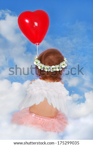 little baby girl with wings sitting on cloud and holding heart shaped balloon - stock photo