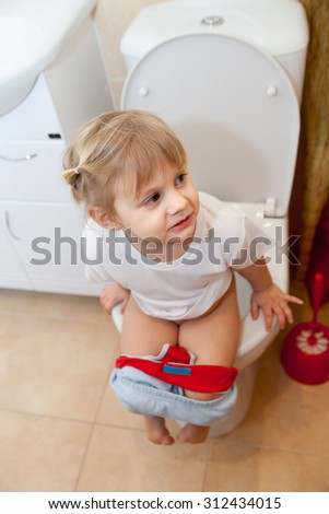 Little baby pissing on   toilet - stock photo