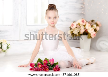 little ballerina with a bouquet of pink tulips, March 8 - stock photo