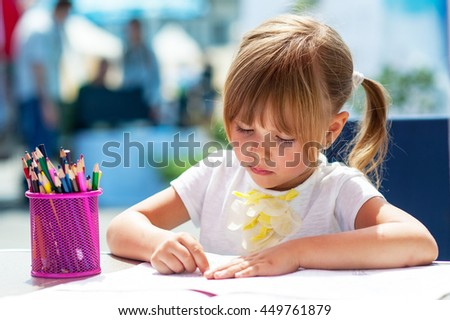 Little beautiful girl draws pencil