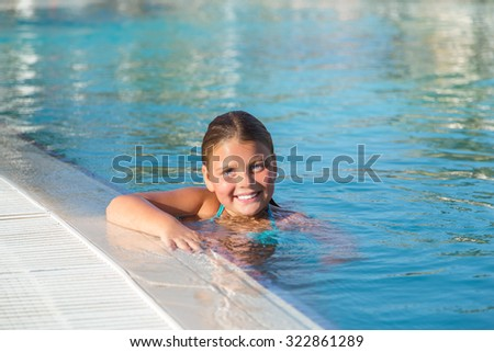 little beautiful pretty happy girl enjoying, smiling, relaxing at swimming pool