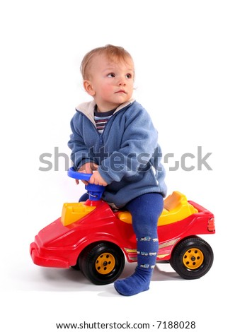 little blond boy driving a red toy car - stock photo