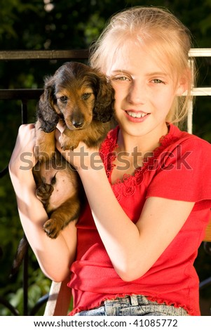 little blonde girl and a loving puppy dachshund - stock photo