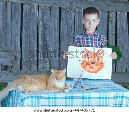 little boy artist with the image of a cat, which he painted.Cat sits next