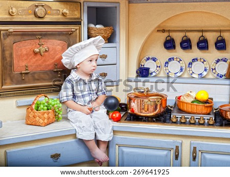 little boy in a suit of the cook sits on a kitchen table - stock photo
