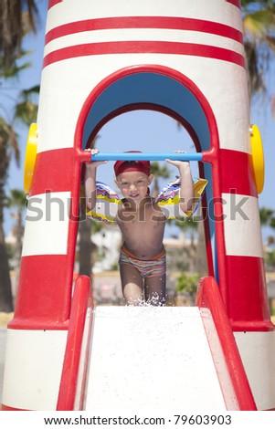 Little boy  in aqua park on the slide - stock photo