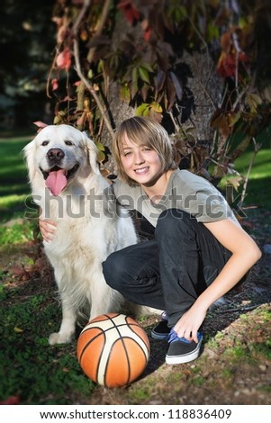 Little boy in the park with a golden retriever dog - stock photo