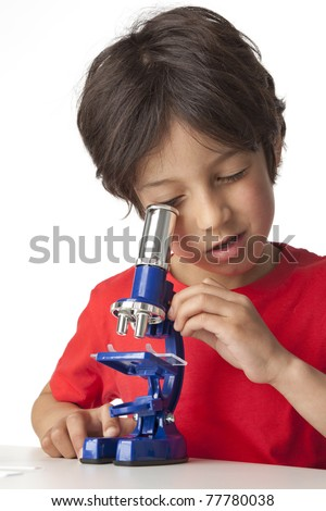 Little boy looking through a microscope on white background - stock photo