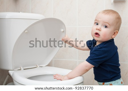 little boy looks in the toilet - stock photo