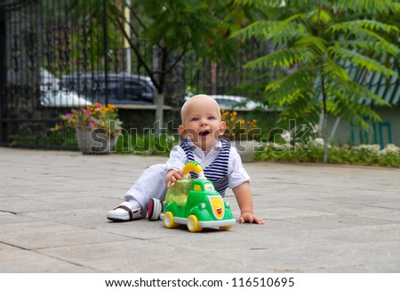 little boy smiling and playing in the toy car on a summer day