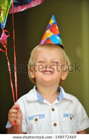 little boy with birthday hat play with balloons