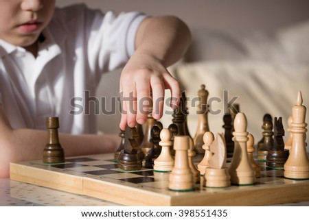 Little clever boy concentrated and thinking while playing chess at home.