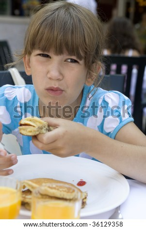 little cute girl seven years old eats a pancake for breakfast.