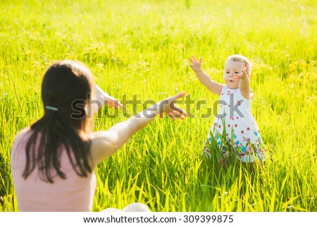 Little daughter happily running towards her mom. People having rest in sunny green meadow on spring or summer day. Mother and baby playing outside. - stock photo