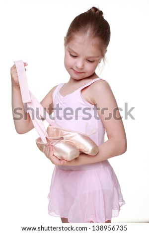 little girl as a ballerina holding ballet shoes (pointes)
