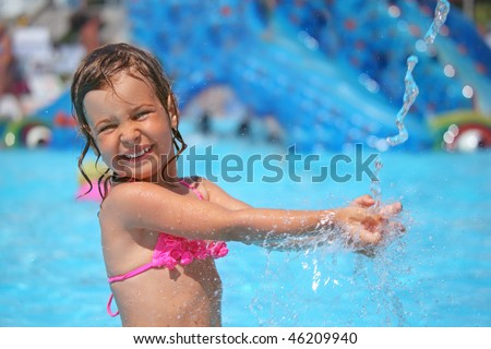 little girl bathes in pool under water splashes in aquapark