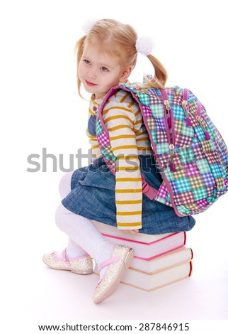little girl  blonde  with a school knapsack on his back  sitting on a stack of books-isolated on white background - stock photo