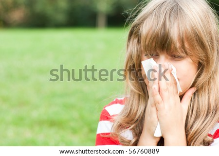 little girl blowing her nose - stock photo