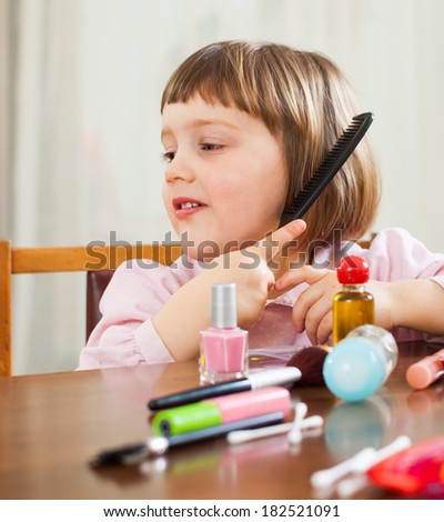 little girl brushing her hair at the table - stock photo