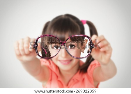 little girl holding eyeglasses, health eyesight concept. Soft focus - stock photo