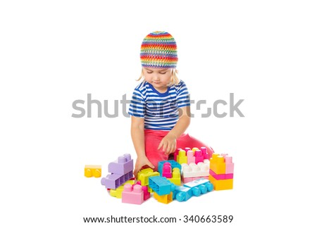 Little girl in a colorful shirt playing with construction toy blocks building a tower. Isolated on a white background. - stock photo