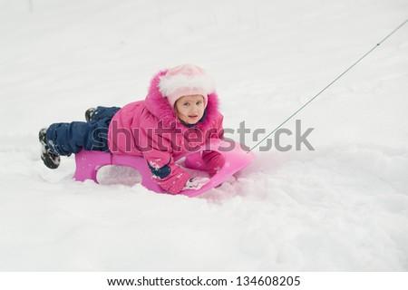 little girl lying on a sled - stock photo