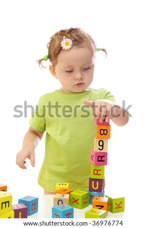 Little girl playing with wooden blocks with letters - stock photo