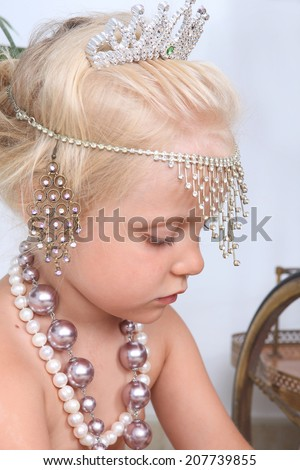 little girl plays with mother's jewelry
