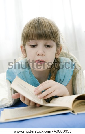 little girl reading a book lying in bed