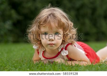 little girl relaxing on grass - stock photo