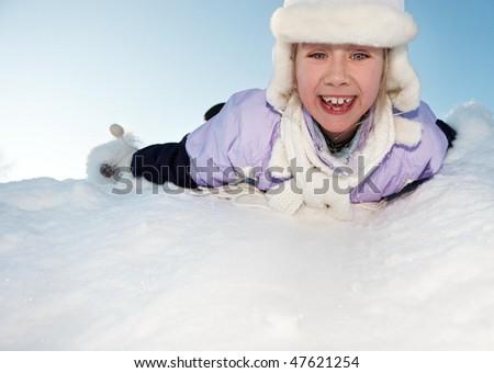 Little girl sliding in the snow - stock photo