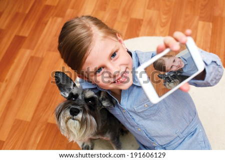 Little girl taking photo of herself and her dog with mobile phone camera  - stock photo
