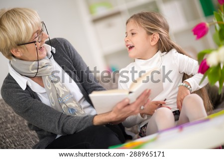 little girl with grandma reading interested book - stock photo